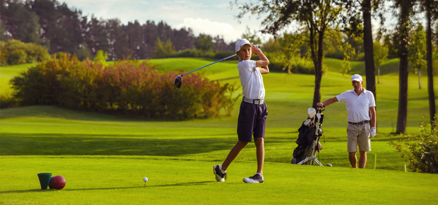 young golfer hitting off tee